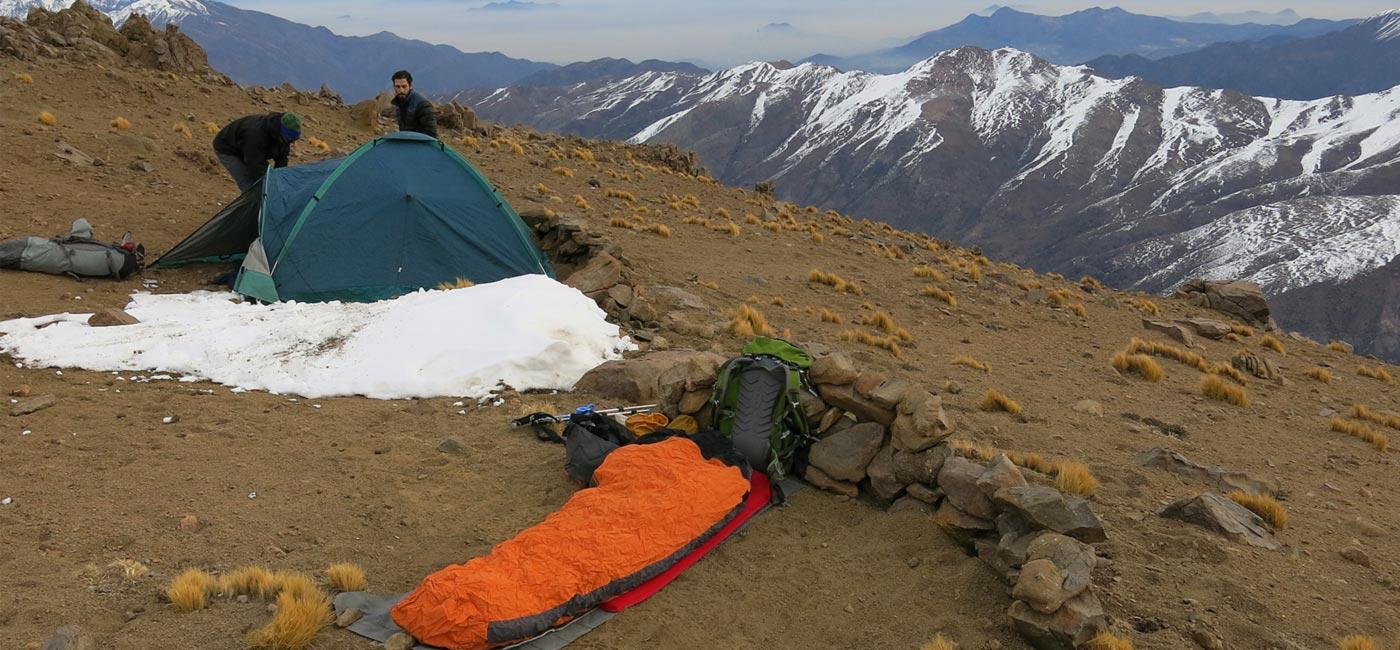 Dos hombres armando una carpa para hacer camping en un montaña.
